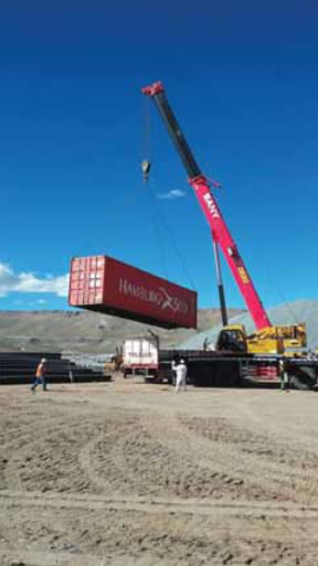 Crane lifting a shipping container with dome parts.